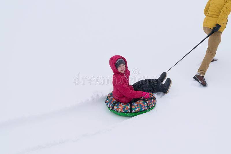 Girl in a red jacket being carried on an inflatable round sleigh in the snow royalty free stock photos