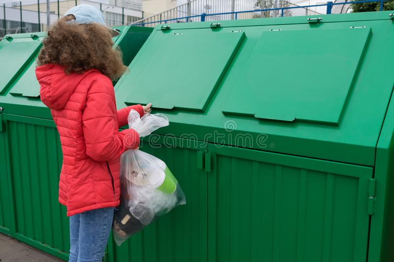 A girl in a red jacket came to throw a bag of waste into a trash  tank. A girl in a red jacket came to throw a bag  of waste into a trash  tank stock image