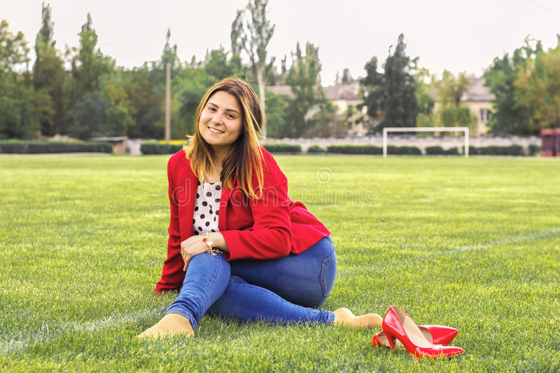 Girl in a red jacket on a green field royalty free stock photos