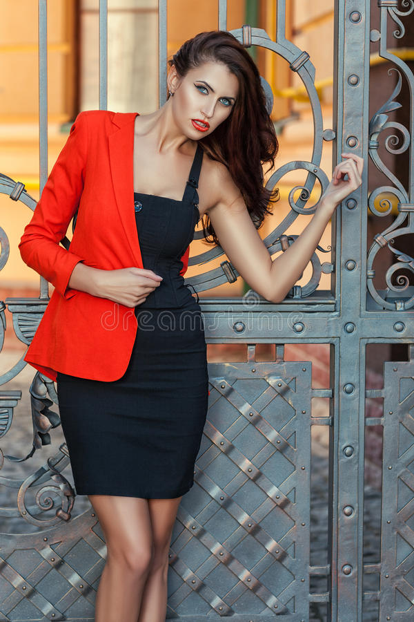 Girl in a red jacket. Portrait of a girl in a red jacket at the gate stock photography