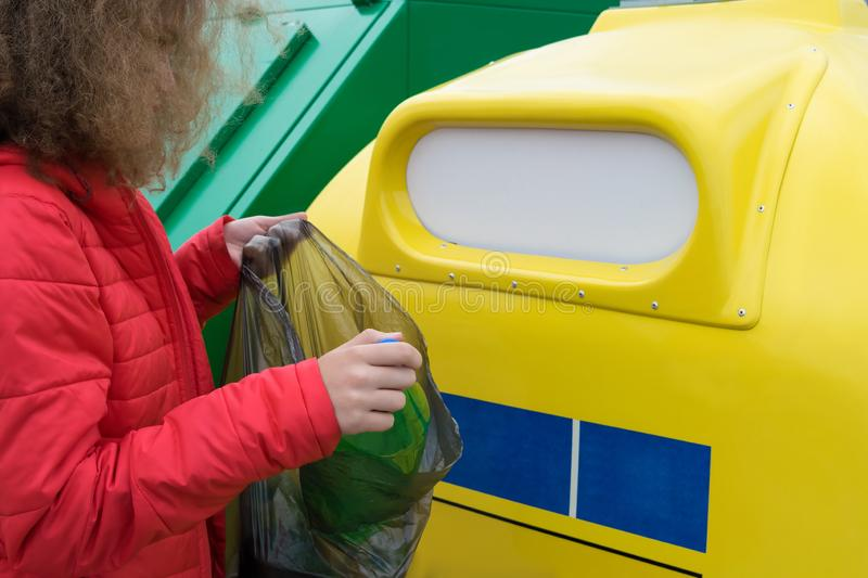 A girl in a red jacket pulls out a plastic bottle from a garbage bag to throw in a special container, sorting garbage. A girl in a red jacket pulls out a plastic royalty free stock photo