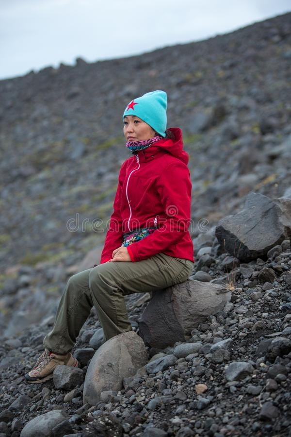 Girl in a red jacket sitting on a stone on the background of a rocky slope royalty free stock image