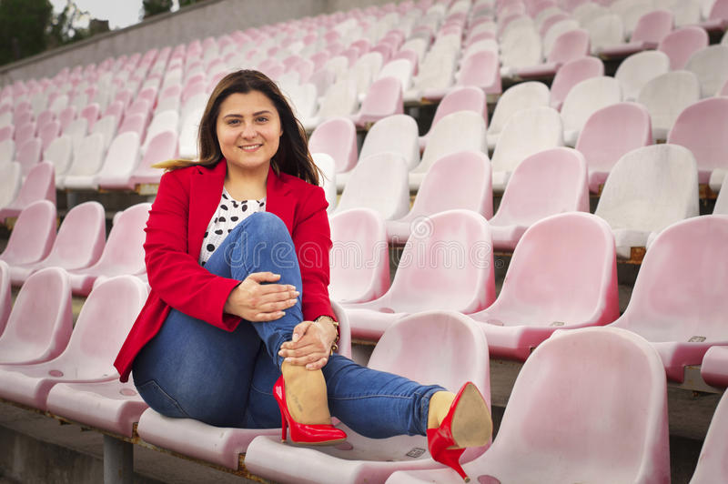 Girl in a red jacket on the stadium seats royalty free stock photography