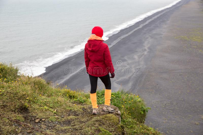 A girl in a red jacket is standing on a cliff above the sea shore stock photography