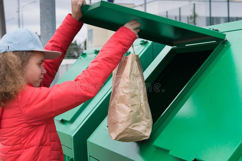 Girl in a red jacket throws a paper bag into the trash tank. Girl in a red jacket throws a paper bag into  the trash tank stock image