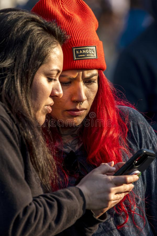 Girl with red Kangol Beany  and friend looks at Cell Phone California. MARCH 24, 2019, LOS ANGELES, CALIFORNIA, USA -  Girl with red Kangol Beany looks at Los stock photos