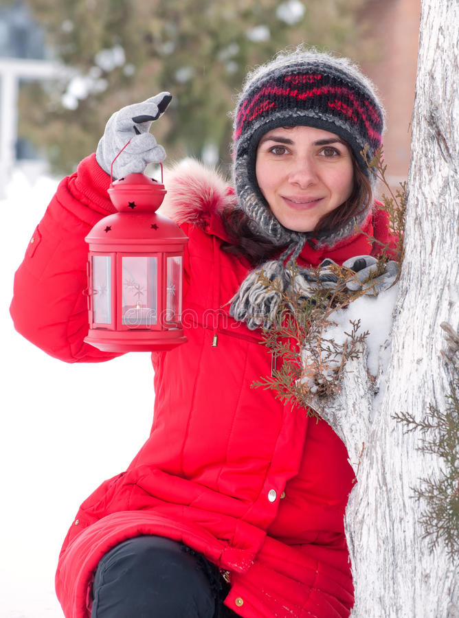 Girl with red lantern in the snow stock images