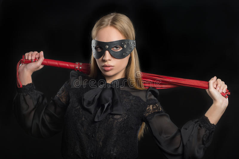 Girl with red leather whip and mask BDSM. Portrait of a girl with red leather whip and mask BDSM royalty free stock photography