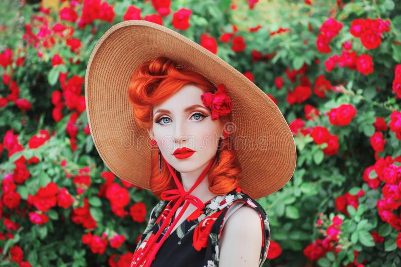 Girl with red lips in rose print dress on summer garden. Spring blossom flower. Redhead model in summer hat on valentines stock photography