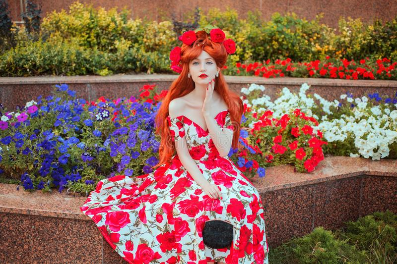 Girl with red lips in summer flower dress with rose print on flowerbed background. Model with red nails and rose flower in. Hairstyle on flower background stock image