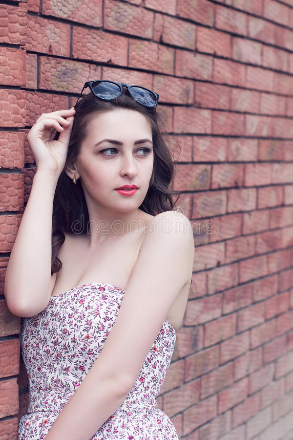 girl with red lips and sunglasses looks aside near the brick wall royalty free stock photos