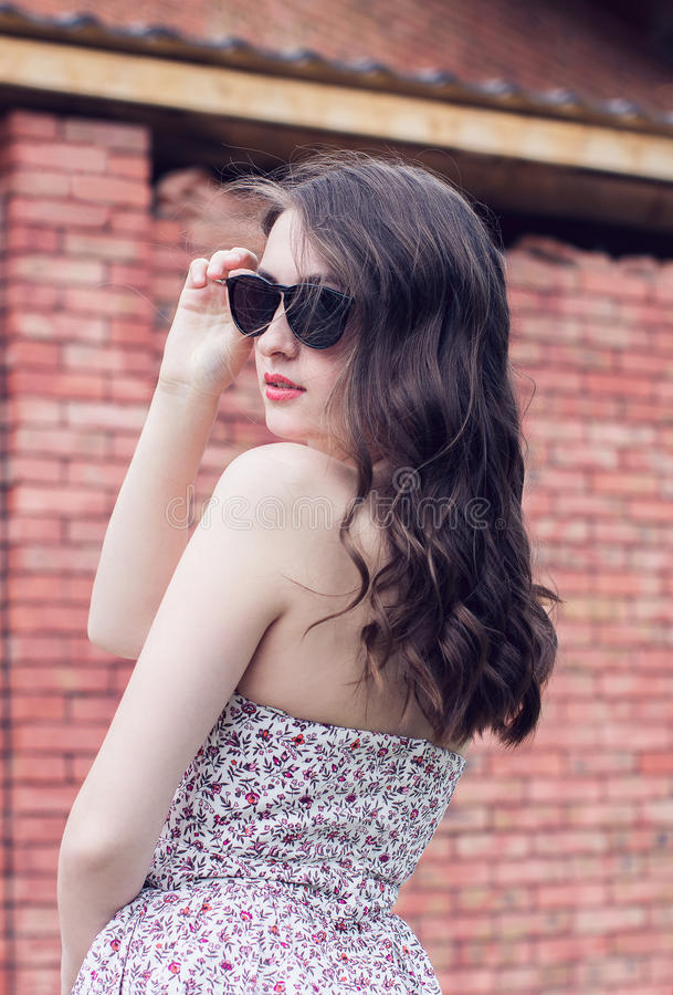 Girl with red lips in the sunglasses turns around near the brick royalty free stock photo