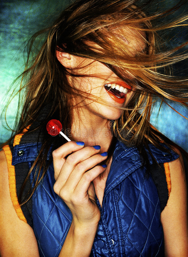Girl with red lollipop and hair in wind stock image