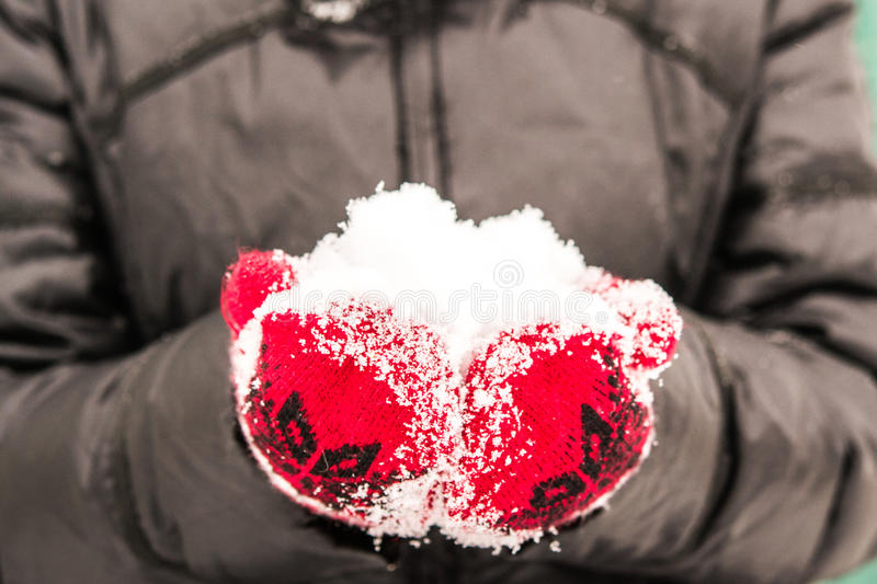 Girl in red mitten holding a handful of snow royalty free stock photography