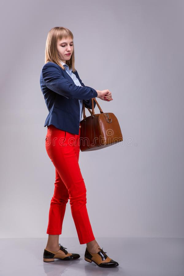 Girl in red pants and with leather bag looking at watch stock image