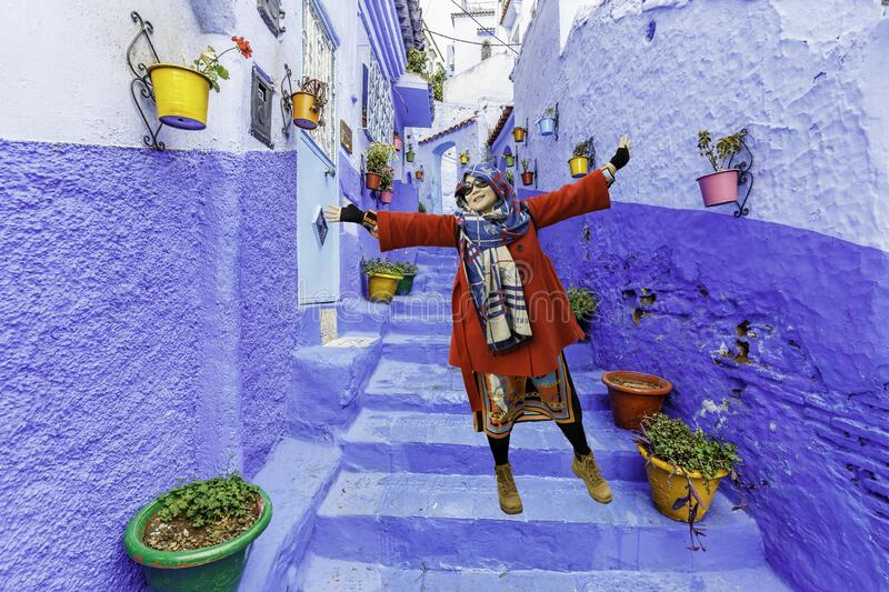 Girl in red posing in the Blue Town Chefchaouen stock photo