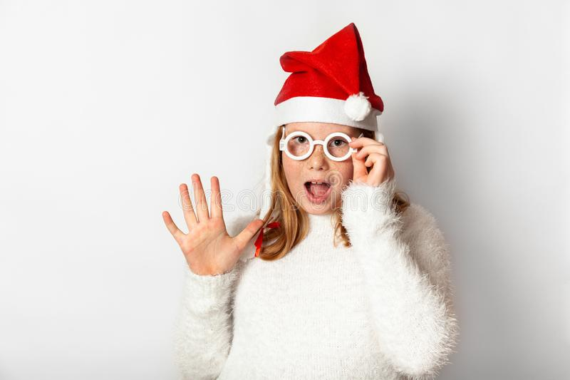 A girl in a red Santa Christmas hat holds a hand with glasses and surprised wow shows a hello symbol,  on a white stock image