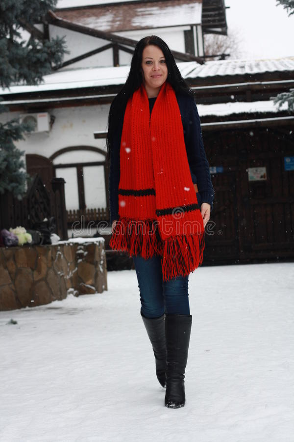 Girl with a red scarf. Beautiful girl with a red scarf in winter walks in the snow royalty free stock image