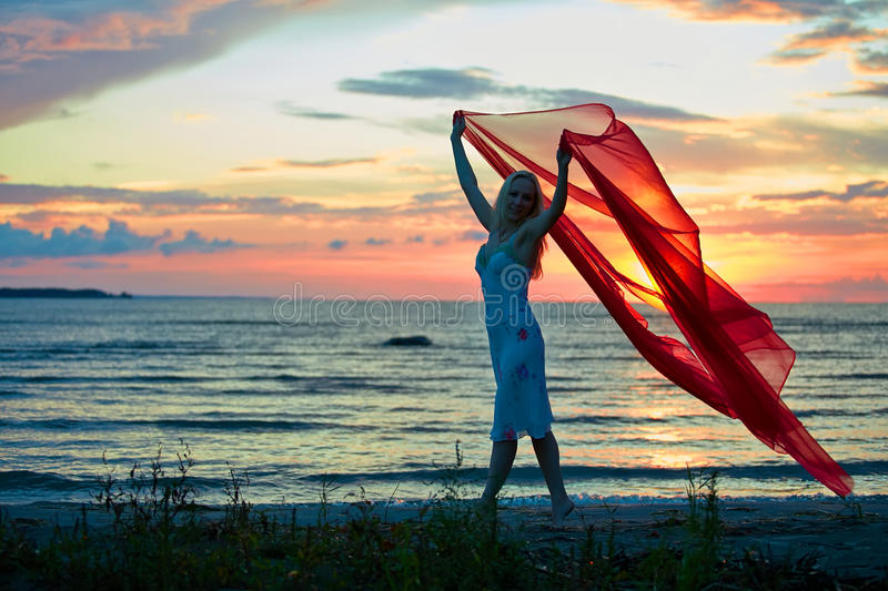 Girl with red scarf. Young woman with hands up holding red scarf in wind on the beach royalty free stock images