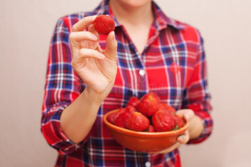 The girl in a red shirt demonstrates a beautiful red strawberry. stock photo