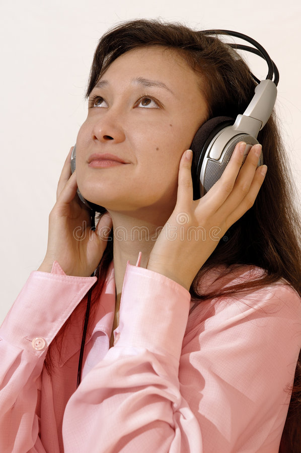 Girl in a red shirt with headphones. A portrait of a beautiful, smiling, young asian girl in a red shirt with headphones listening to the music on the radio royalty free stock photography