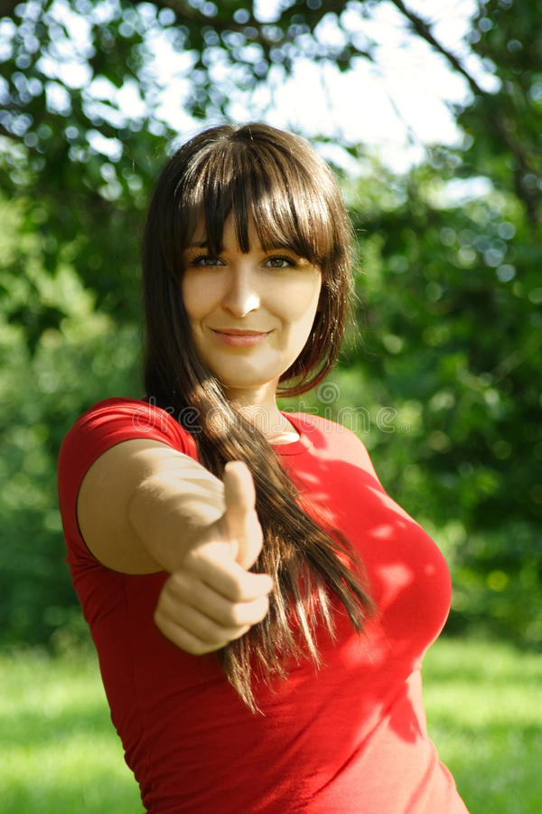 Girl in red shirt making thumbs up gesture