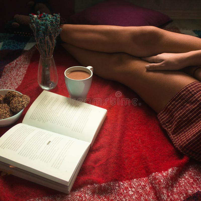 Girl in a red shirt on a plaid reading a book over a cup of coffee stock images