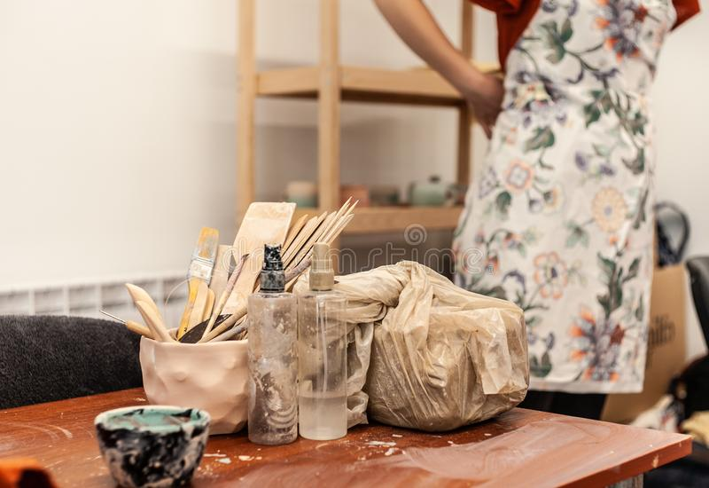 A girl in red shirt putting on white pinafore while staring in pottery studio, tools for pottery located nearby on wooden table royalty free stock photo