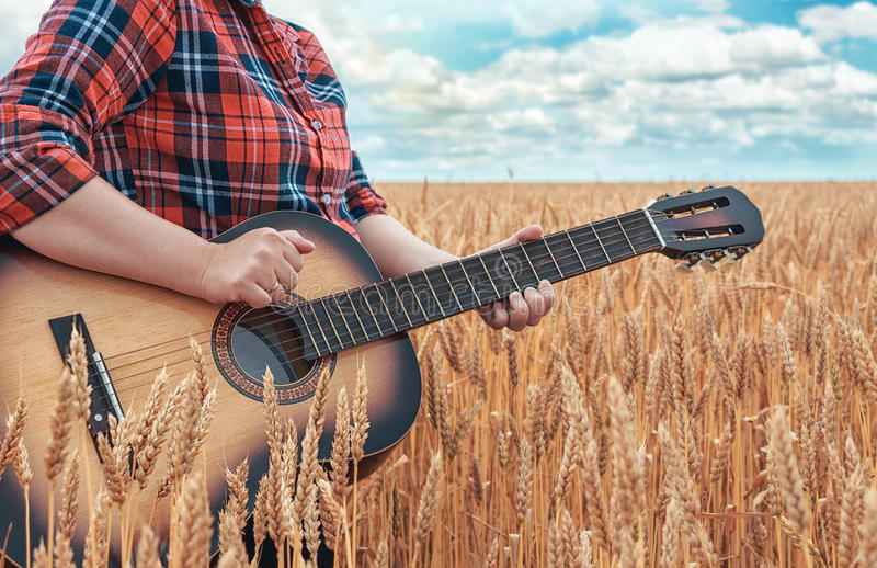 Girl in the red shirt in wheat field plays the acoustic guitar. Beautiful nature at bright sunny summer day. stock photography