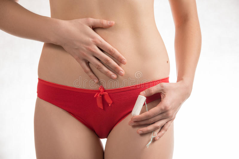 Girl in red shorts holding a hygienic tampons and pads during me royalty free stock images