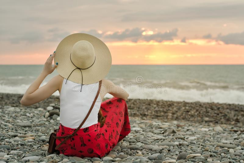 Girl in red skirt and hat sits on the seashore, sunset time. View from the back.  stock photography