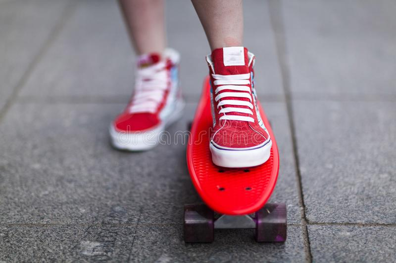 Girl in red sneakers put her foot on a skateboard. Close-up royalty free stock photography