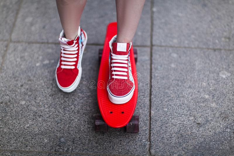 Girl in red sneakers put her foot on a skateboard. Close-up royalty free stock images
