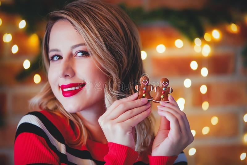 Girl in red striped sweater with gingerbread man. Portrait of a young girl in red striped sweater with gingerbread man at Christmas lights background royalty free stock image