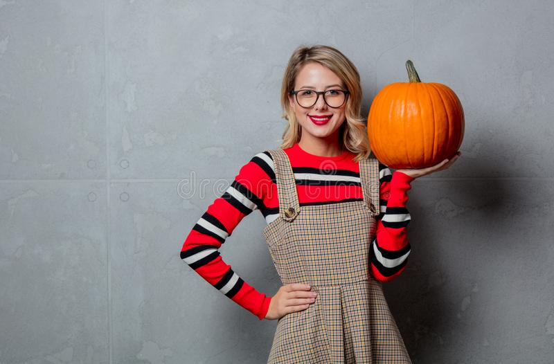 Girl in red striped sweater with halloween pumpkin royalty free stock photo
