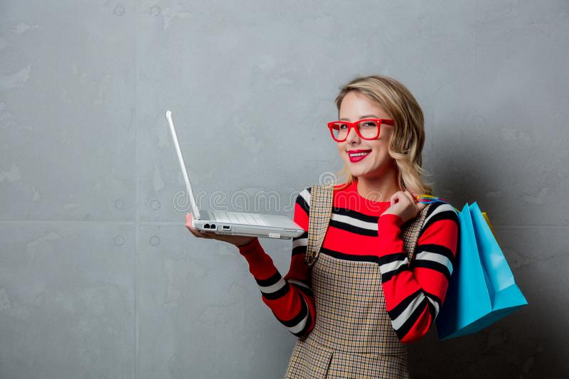 Girl in red striped sweater with shopping bags and laptop computer royalty free stock photo