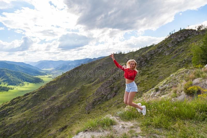 A girl in a red top and blue shorts jump up on the edge of a cliff in the Altai Mountains, below are green fields with trees and royalty free stock image