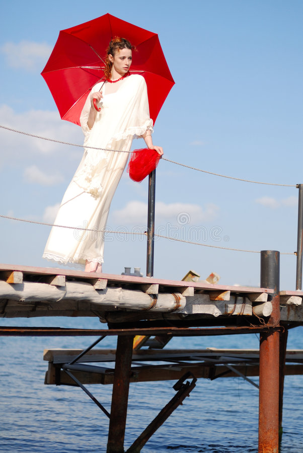 Girl with red umbrella. On the wharf royalty free stock photo