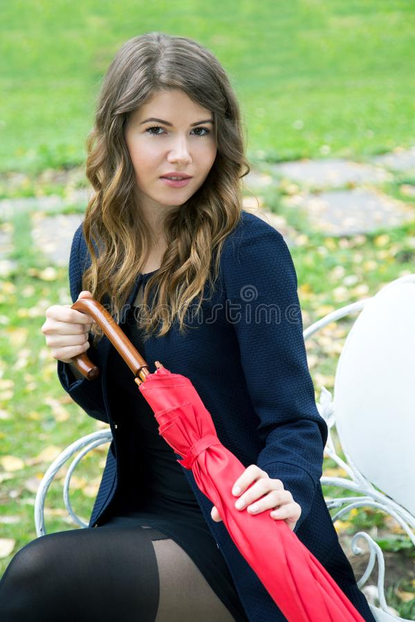 Girl with a red umbrella in her hands. On a park bench royalty free stock photography