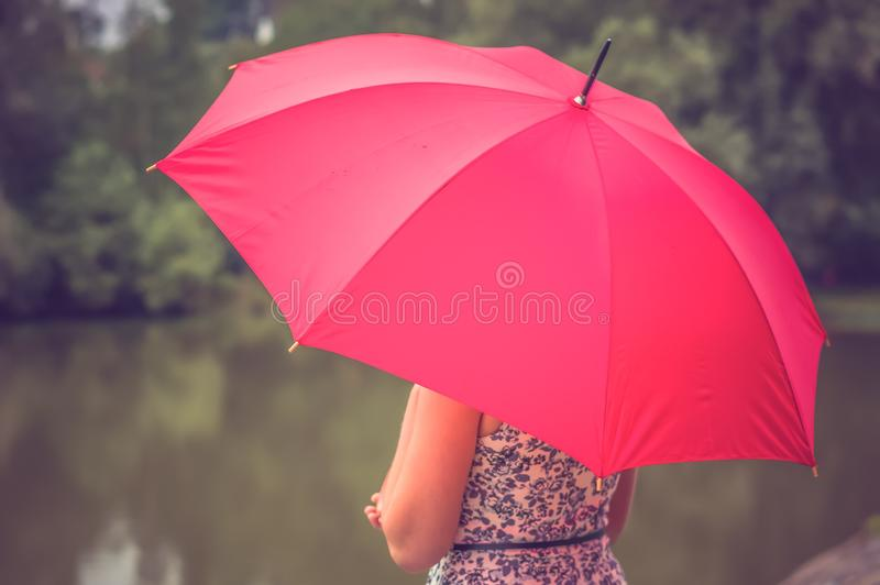 Girl with red umbrella near the pond. Beautiful girl with red umbrella near the pond - retro and vintage style royalty free stock images