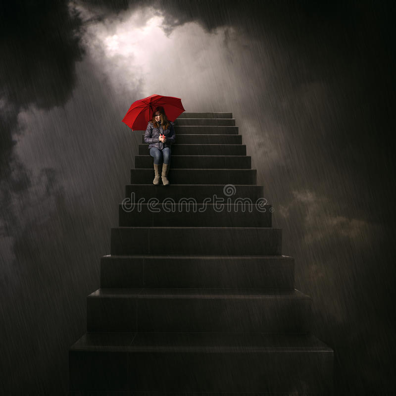 Girl with red umbrella sitting on stairway. Girl with red umbrella sits on the stairs with dark storm clouds in the background stock photography