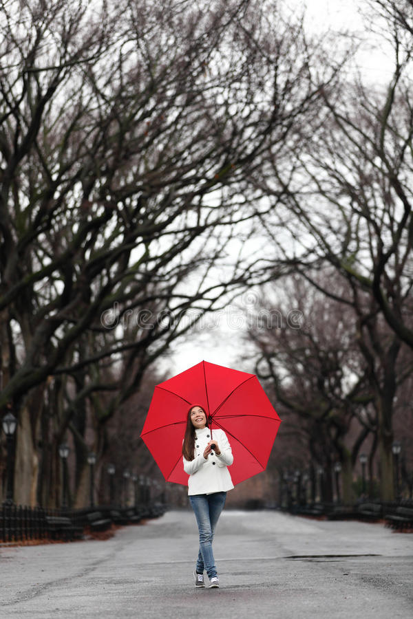 Girl with red umbrella walking in park in fall. Happy smiling multiracial Asian woman walking cheerful with red umbrella in Central Park, Manhattan, New York royalty free stock photos