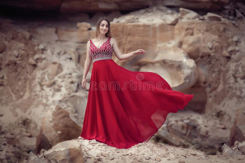 Girl in a red waving dress on a background of stones royalty free stock image