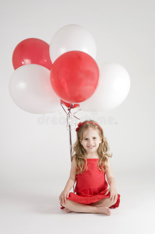 Girl with red and white balloons royalty free stock image