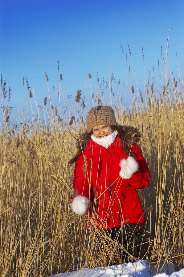 Girl in a red winter jacket. Stands in canes royalty free stock image