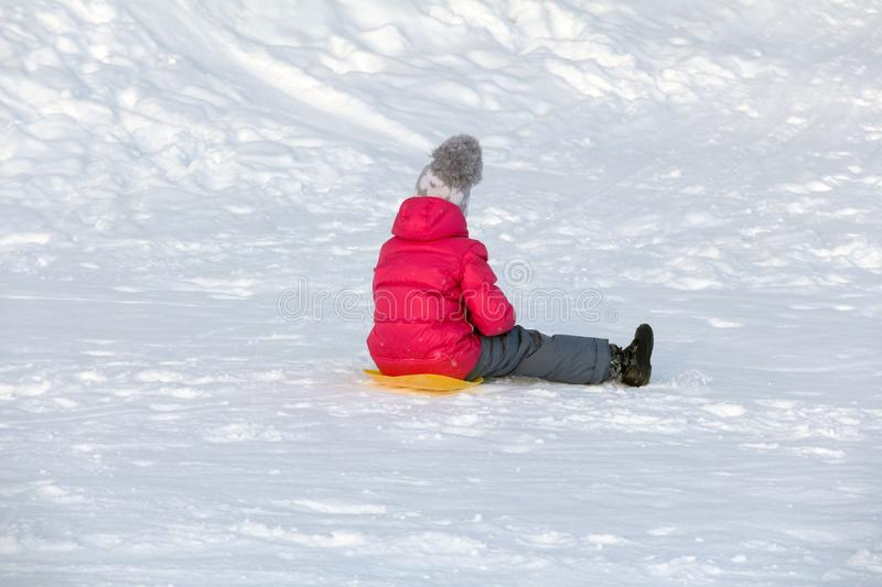 Girl in a red winter jacket and winter pants sits on the snow royalty free stock images