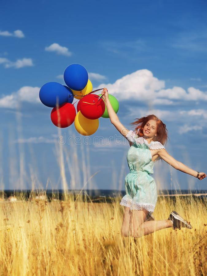 Girl redhead jumping with ballons at the yellow spikelets and blue sky royalty free stock images