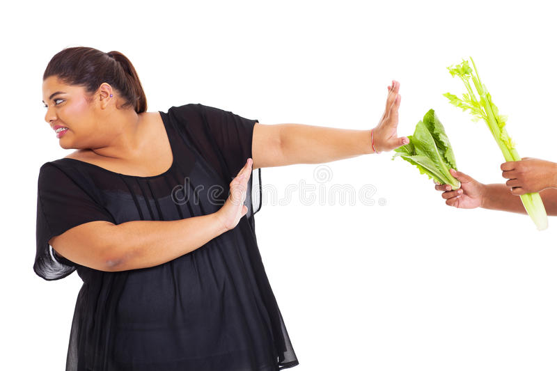 Girl refuse vegetables. Overweight teen girl refuse to have vegetables stock image