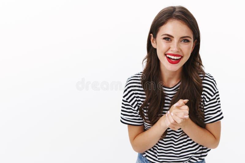Girl Reibung Hände gutes Geschäft, dankbare Hilfe Freund, amüsiert und fröhlich lächelnd erfreut, tragen gestreiftes T-Shirt, rot lizenzfreies stockfoto