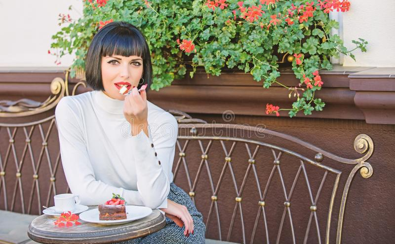 Girl relax cafe with cake dessert. Gourmet concept. Pleasant time and relaxation. Delicious gourmet cake. Woman. Attractive elegant brunette eat gourmet cake royalty free stock photo
